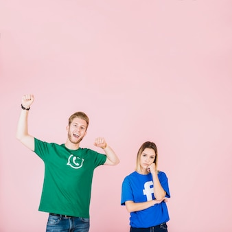 Happy man raising his arms beside upset woman on pink background