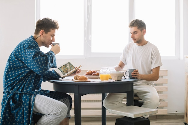 Happy man reading book sitting in front of his friend having breakfast
