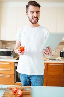キッチンでタブレットコンピューターでレシピを読んで幸せな男
