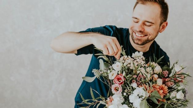 花の花束を再配置する幸せな男
