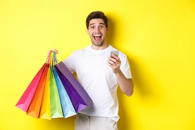 행복한 사람은 구매에 대한 캐쉬백을 받고, 스마트 폰과 쇼핑백을 들고, 흥분된 미소, 노란색 벽 위에 서서