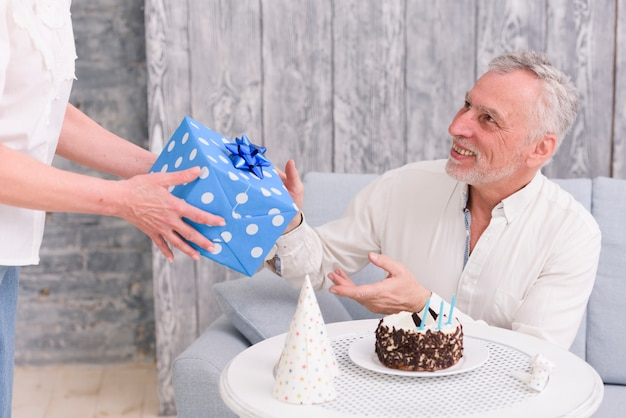 Happy man receiving birthday gift from his wife near cake and party hat on table