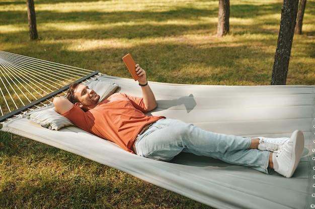 태블릿으로 해먹에서 휴식을 취하는 행복한 사람