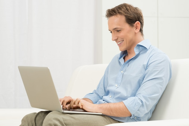 Счастливый человек, расслабляющий на диване с помощью компьютера