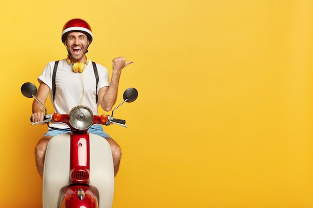 Happy man rides a scooter, shows direction away, points thumb right on blank space over yellow background, dressed in casual wear and helmet, uses headphones, has cheerful face expression