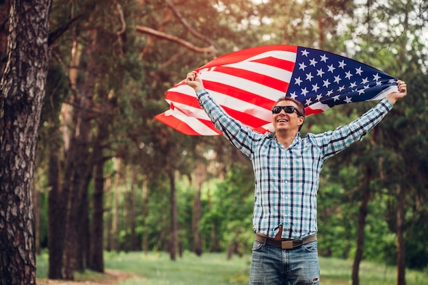 夕暮れ時の公園で米国旗を持って走っている幸せな男