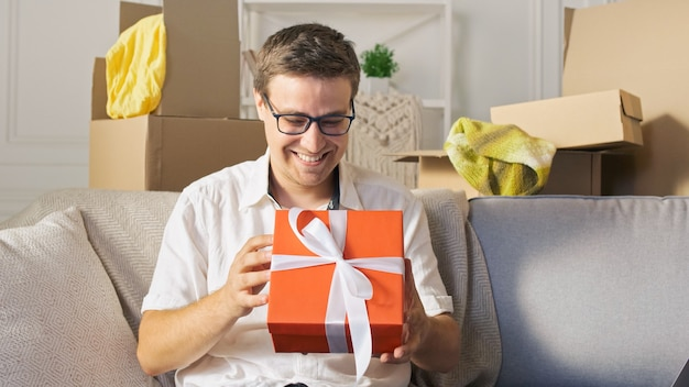 A happy man satisfied by a quick delivery unpacking of order from online shops