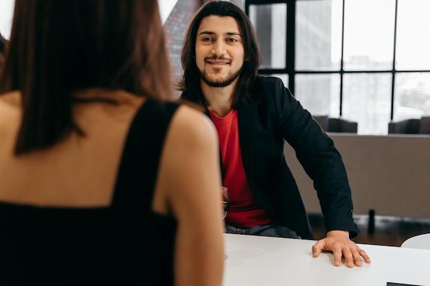 幸せな男は彼の最愛の女性に乾杯を言い、彼の手にグラスワインを持っています。高品質の写真