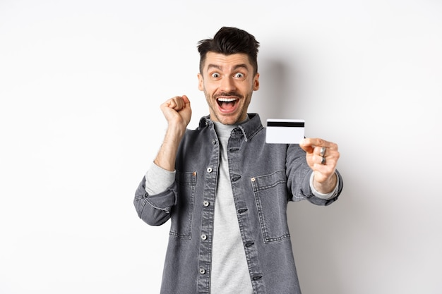 Happy man scream from excitement and show plastic credit card, recommending bank, standing on white background.
