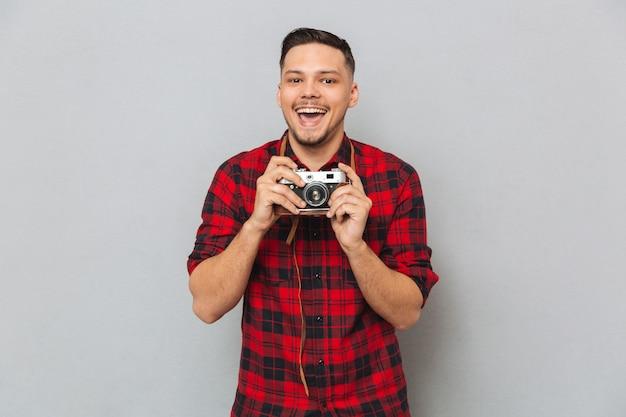 Uomo felice in camicia che fa foto sulla retro macchina fotografica