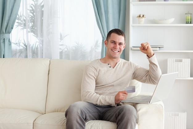 Happy man shopping online with the fist up in his living room