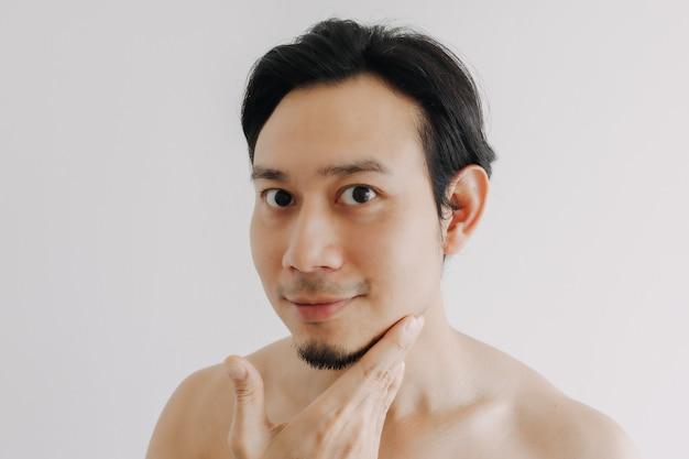Счастливый человек показывает свое лицо, применяя средство по уходу за кожей