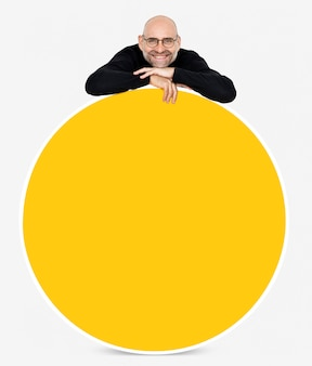 Happy man showing a round yellow board