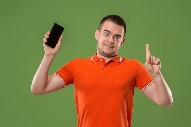 The happy man showing at empty screen of mobile phone against green wall.