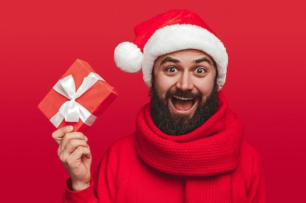 Счастливый человек показывает подарочную коробку во время рождественской вечеринки