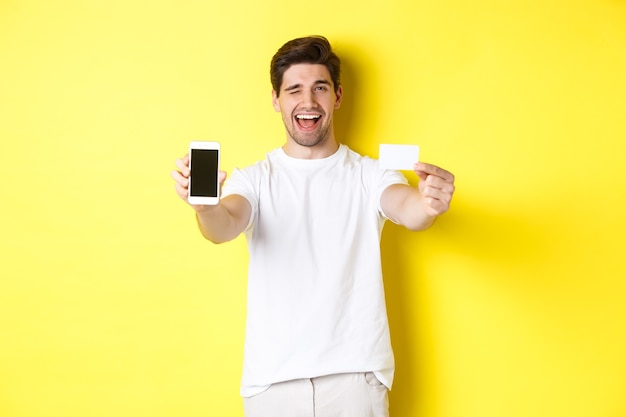 Happy man showing good online offer on mobile phone screen, holding credit card and winking, standing over yellow background.