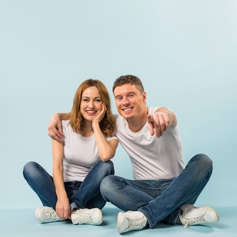 Happy man showing her girlfriend something with pointing his finger to camera