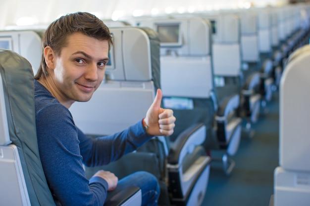 Счастливый человек показывает палец вверх внутри самолета