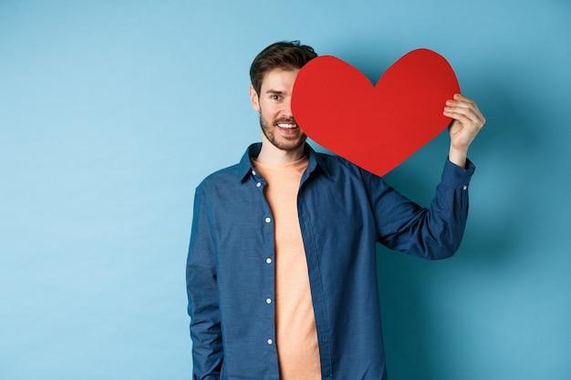 バレンタインの心を示し、笑顔で幸せな男は、青い背景の上に立って、恋人の日にロマンチックな贈り物をします。