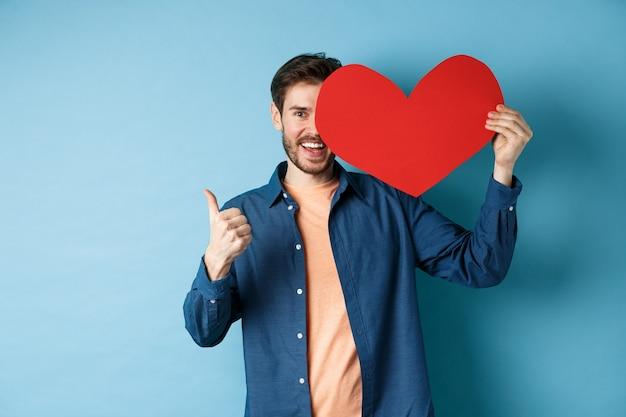 파란색 배경 위에 서 발렌타인 마음과 엄지 손가락 업 제스처를 보여주는 행복 한 사람.