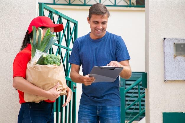 Счастливый человек подписывает для получения заказа из продуктового магазина, держа буфер обмена и улыбается. почтальонка в красной форме держит бумажный пакет с овощами. служба доставки еды и концепция почты