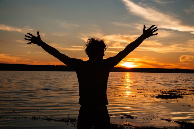 ビーチで夕日の背景に手を上げて幸せな男のシルエット