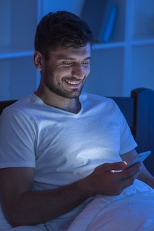 The happy man sit with a phone in the bed. night time