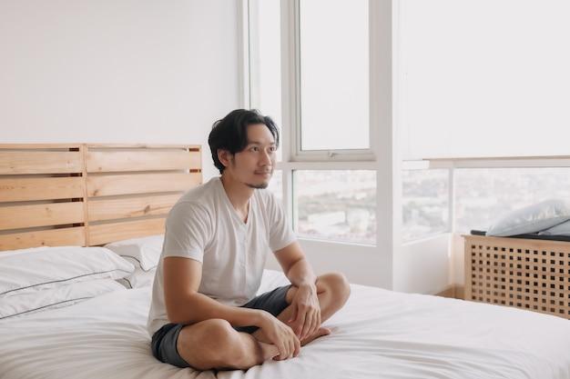 Счастливый человек сидит и отдыхает на своей кровати в своей квартире
