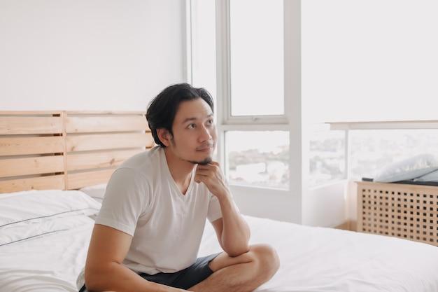 幸せな男は彼のアパートの彼のベッドに座ってリラックス