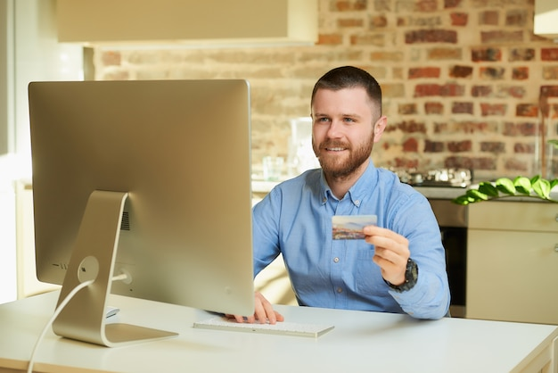 A happy man sits in front of the computer and types a credit card information on an online store at home