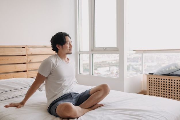 Happy man sits and relax on his bed in his apartment