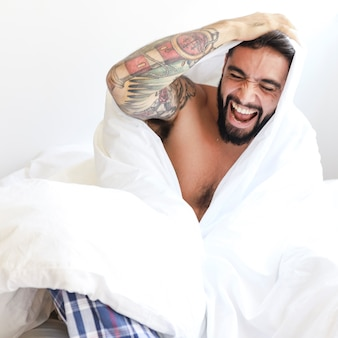 Happy man sitting on bed