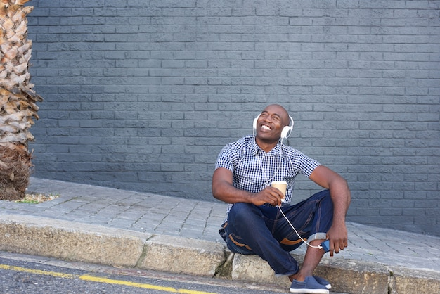Happy man sitting by a street and listening to music