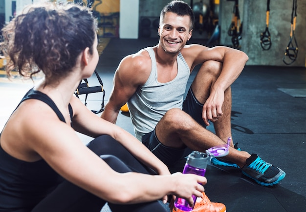 Happy man sitting on floor looking at woman in gym