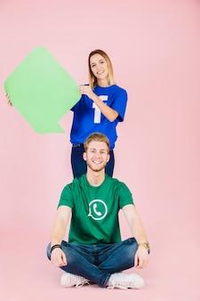 Happy man sitting in front of woman holding empty green speech bubble