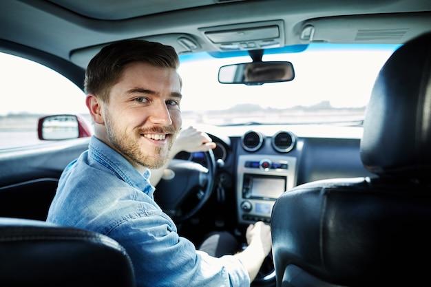 車の中で座って、カメラを見て、笑顔、肖像画、運転の幸せな男。