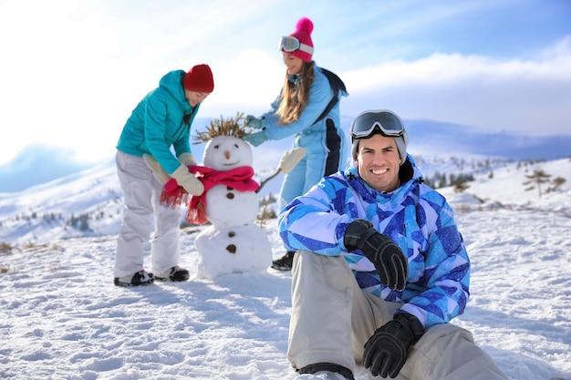 Счастливый человек, сидящий на заснеженном холме на горнолыжном курорте. зимние каникулы