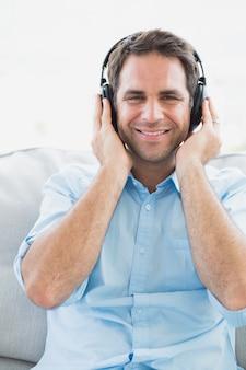 Счастливый человек, сидя на диване, слушать музыку, улыбаясь на камеру
