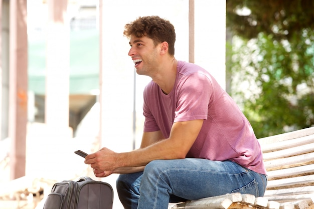Happy man sitting on park bench with suitcase and cellphone
