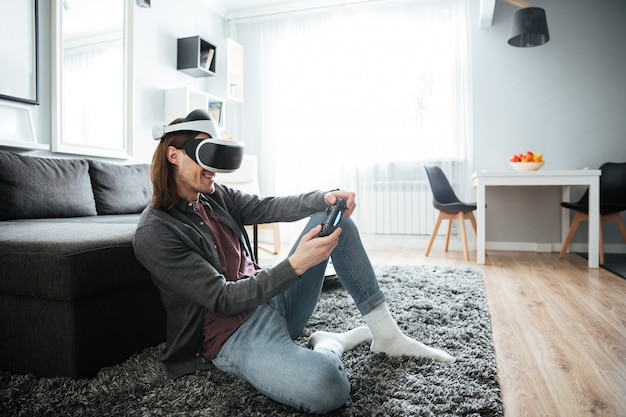 Happy man sitting play games with virtual reality glasses