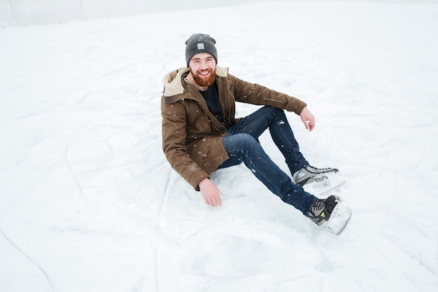 Happy man sitting on the snow in ice skates