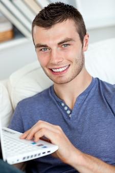 Happy man sitting on the sofa using his laptop