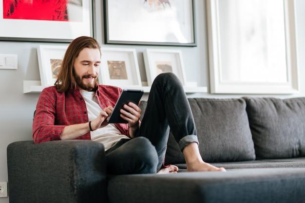 Uomo felice che si siede sul sofà e che per mezzo della compressa a casa