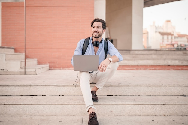 Happy man sitting on staircase with laptop