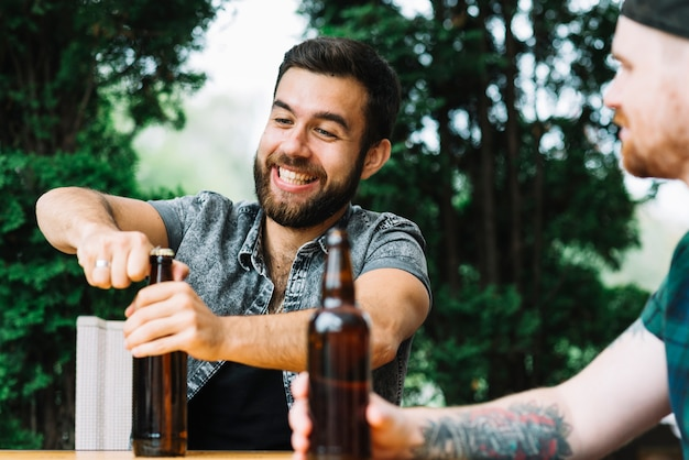 Happy man sitting with friend opening the beer bottle at outdoors