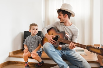 Happy man sitting with his son playing guitar