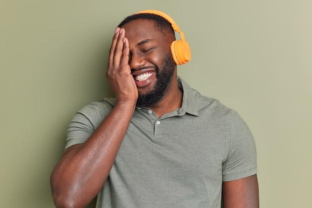 Счастливый человек широко улыбается, делает лицо ладонью веселый вид, слушает музыку в оранжевых беспроводных наушниках, имеет хорошее качество звука, одет в простую футболку, позирует в помещении