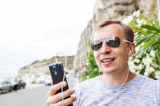 행복한 사람이 웃고 해변에서 휴대 전화로 전화