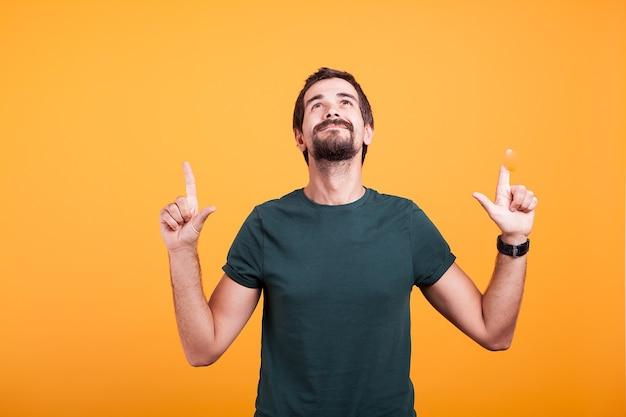 笑顔と彼の指で上向きの幸せな男。あなたのテキストと広告宣伝のために利用可能なコピースペース。オレンジ色の背景で撮影