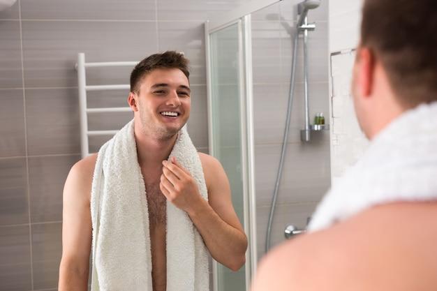 행복한 남자는 거울을 보고 현대적인 타일 욕실에 서 있는 동안 절차를 씻은 후 어깨에 수건을 들고 웃고 있다